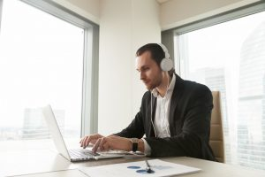 Businessman takes part in online meeting, conference, live stream, communicates with colleagues or partners via internet telephony. Guy listening music while working on laptop in office. Online study