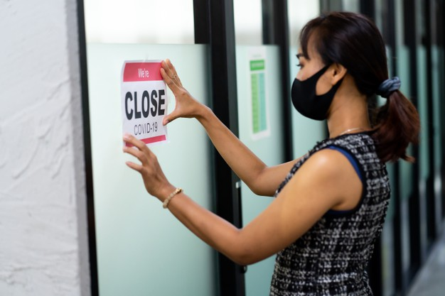 asian-female-wearing-medical-mask-puts-temporary-closed-due-covid-19-pandemic-sign-banner-door-windows-office_38052-245