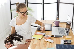 front-view-woman-holding-cat-working-from-home_23-2148557210