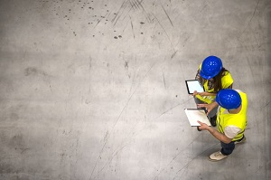 top-view-two-industrial-workers-wearing-hardhats-reflective-jackets-holding-tablet-checklist-gray-concrete-floor_342744-1461