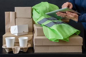delivery-service-courier-box-green-vest-cup-coffee-hand-tablet-online-workplace_159341-1952