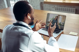 doctor-advising-patient-online-with-laptop_155003-8508
